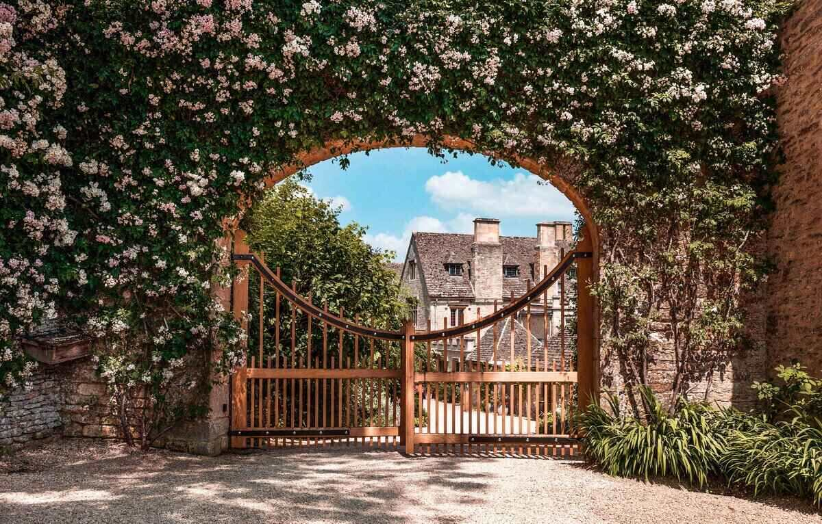 Rose-covered arshway at Asthall Manor, Cotswolds